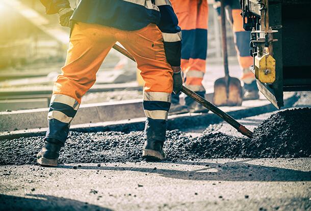 man in work clothes shoveling asphalt