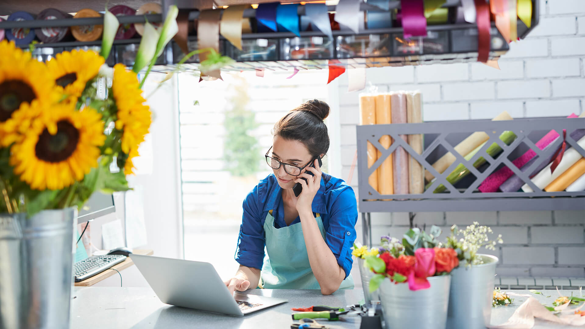 Woman doing business from her laptop in shop
