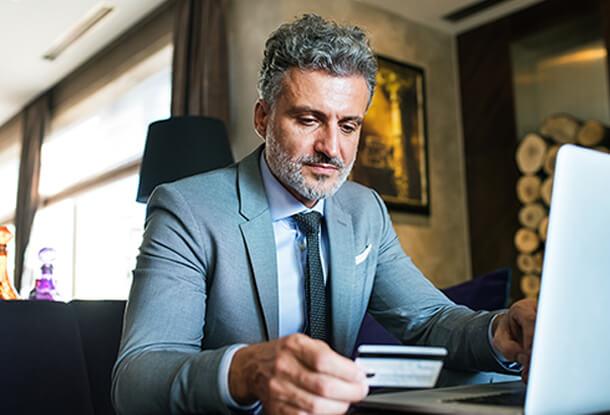 Business man using card at laptop