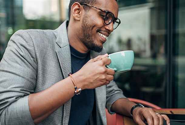 Business man with glasses drinking coffee while using laptop