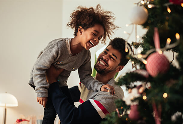 Father holding child near Christmas tree